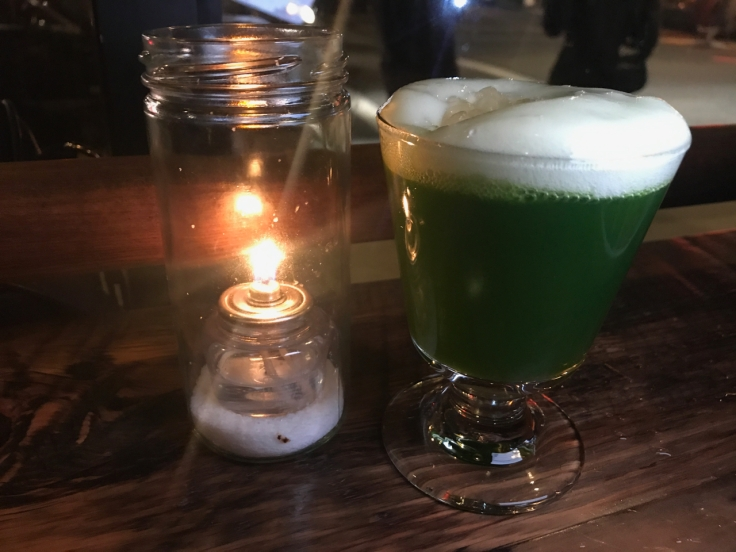 A photo of the dark green aloe vera cocktail at The Snug SF in San Francisco, California. The drink is made with tequila, aloe vera, wheatgrass and lime.