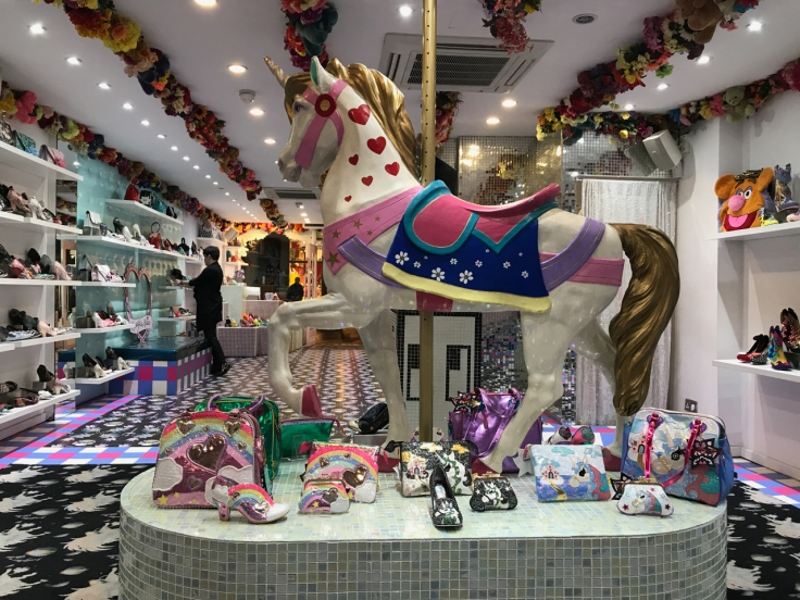 A photo of the inside of Irregular Choice's flagship store in London, England. There's a full size carousel horse surrounded by all kinds of cool crazy shoes, purses, bags and high heels.