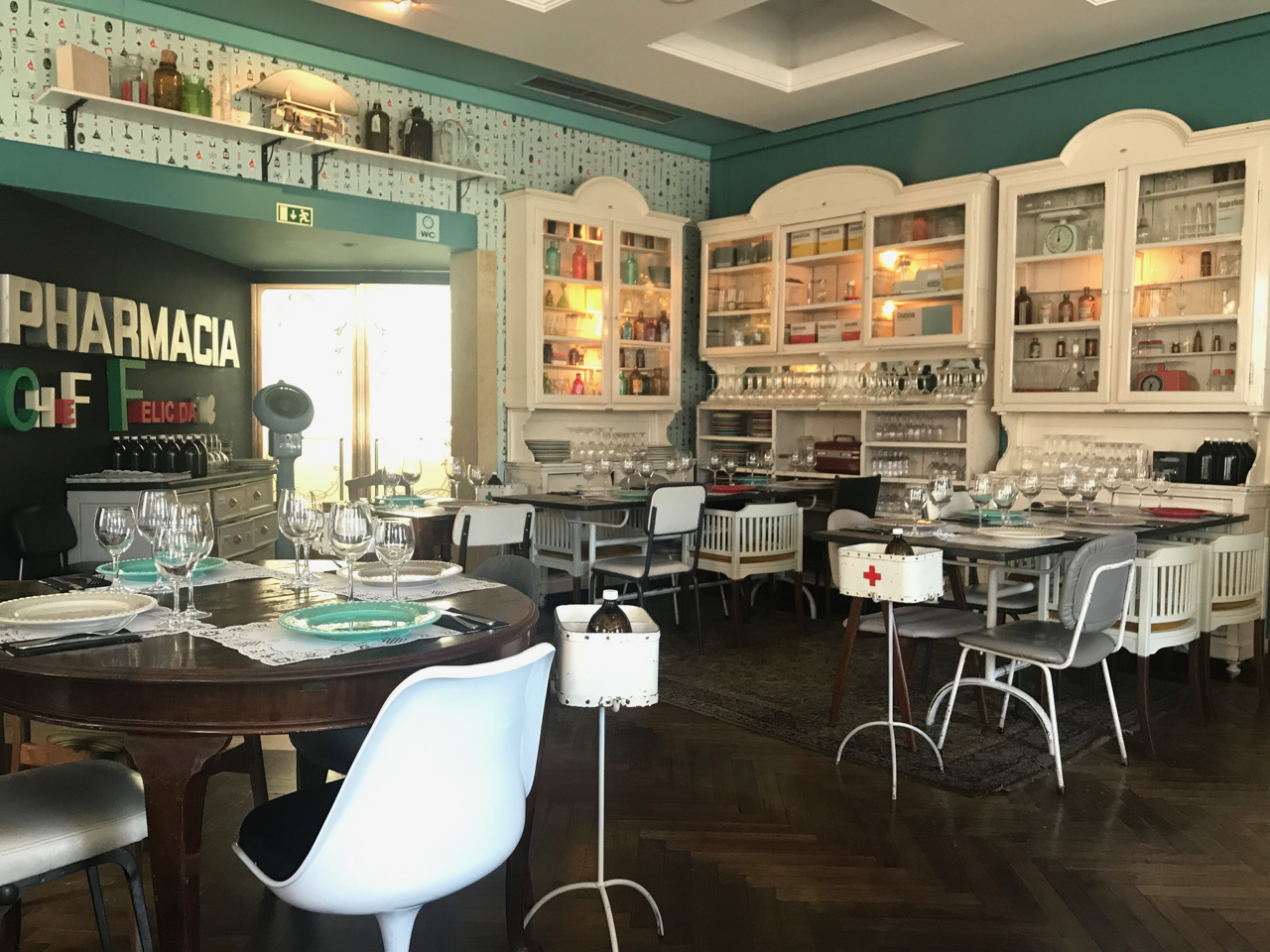 A photo of the tables, chairs and wallpaper (all of which are pharmacy themed) at Pharmacia restaurant in Lisbon, Portugal. All of the shelves and cabinets are filled with old drug bottles and other objects you might find at a pharmacy.