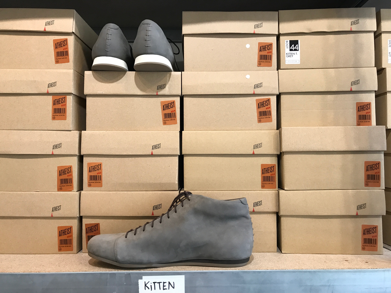 A photo of kitten testicle grey boots and sneakers in their boxes at Atheist Shoes in Berlin, Germany.