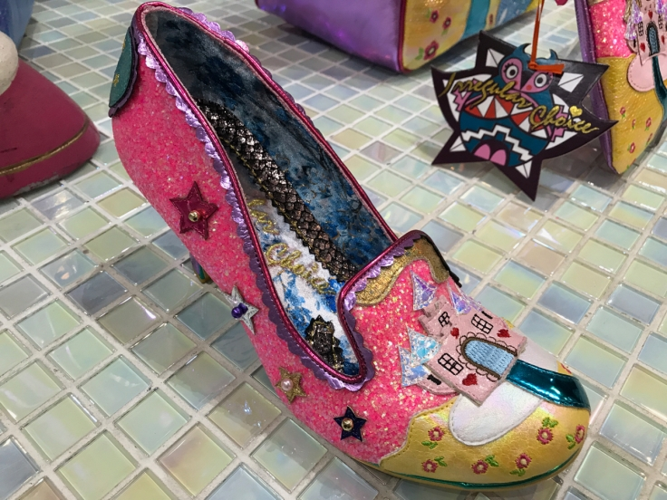 A photo of hot pink glittered shoes called the little misty at the Irregular Choice shoe store in London, England. The shoes have a little embroidered castle palace design on them and stars sewn around the shoe.