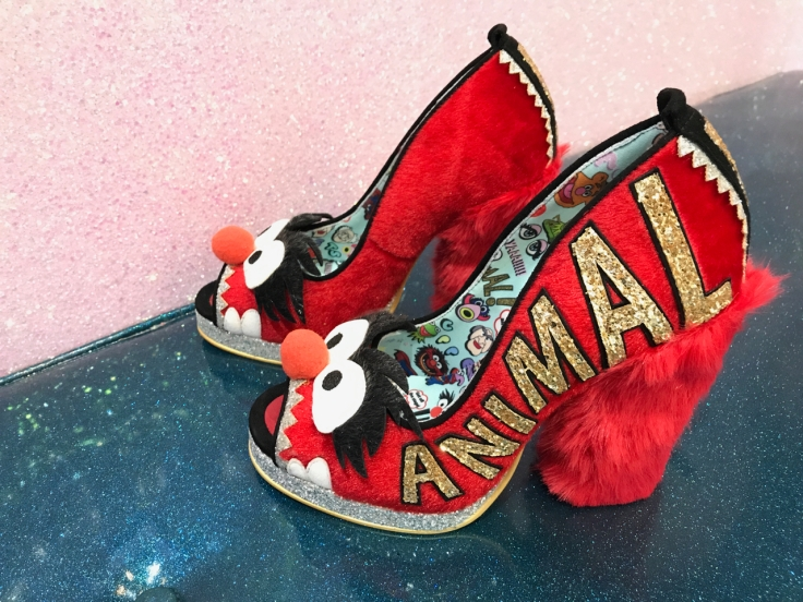 A photo of bright red shoes that have a fuzzy red high heel at Irregular Choice in London, England. The louder, louder shoes were inspired by animal a character on Sesame Street.