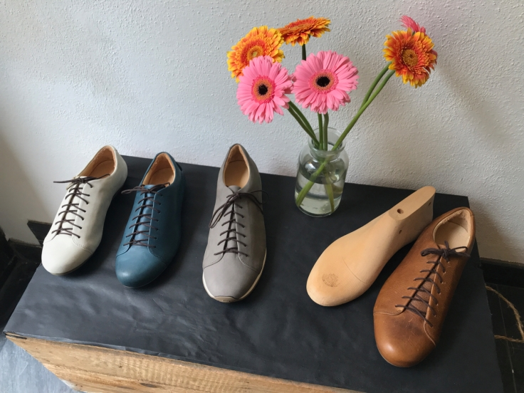 A photo of Nabakov white cream shoes, das petrol blue shoes, kitten testicle grey sneakers and a das cognac shoe on display a top a wooden box bench beside brightly colored flowers at Atheist Shoes in Berlin, Germany.