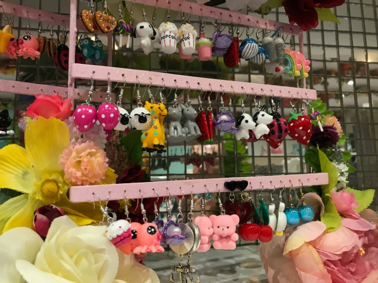 A photo of an earring display at the Irregular Choice flagship store in London, England. There are puppy dog earrings and popcorn earrings, cupcake and whale earrings, earrings with rainbows and giraffes and strawberries and even teddy bear and sheep earrings.