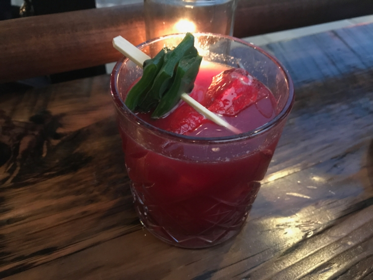 A photo of the blood red hued prickly pear cocktail at The Snug SF in San Francisco, California. The drink is made with mezcal, amaro, nopales, prickly pear, habanero and lime.