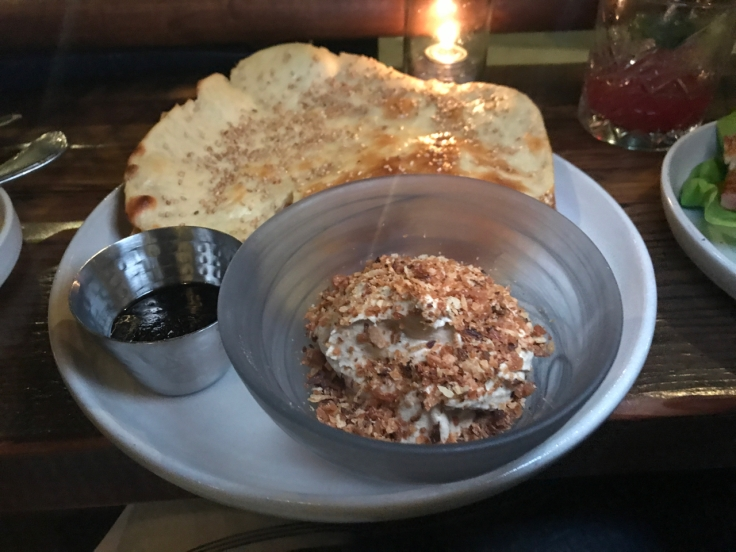 A photo of the sesame naan and shiitake mushroom hummus at The Snug SF in San Francisco, California. The dish also features burnt leeks (on the side) and roasted garlic.
