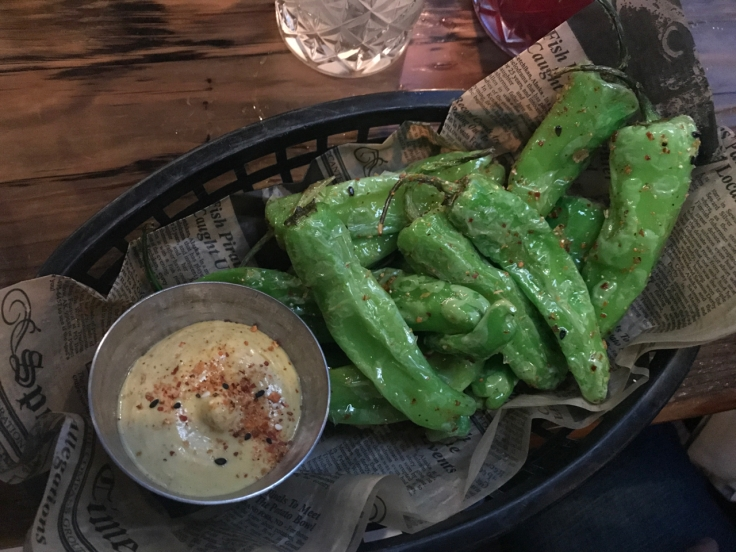 A photo of a black basket filled with green steamed shishito peppers served with sweet corn togarashi dip at The Snug SF in San Francisco, California.