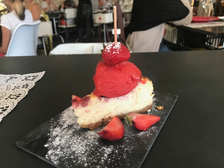 A slice of goat cheese pie topped with strawberry slushie is served for dessert at Pharmacia restaurant in Lisbon, Portugal. (Tarte de queijo cabra com granizado de morango)