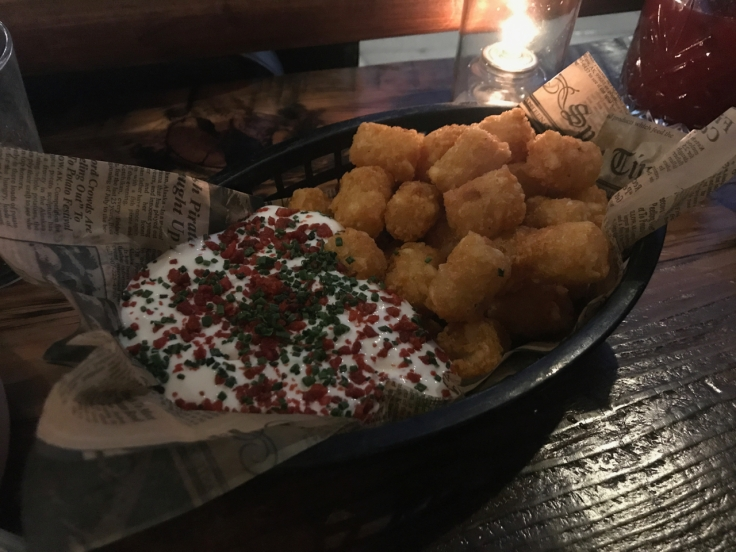 A photo of a black basket filled with tater tots at The Snug SF in San Francisco, California. On the side is a horseradish sour cream topped with chives and Bac-Os.