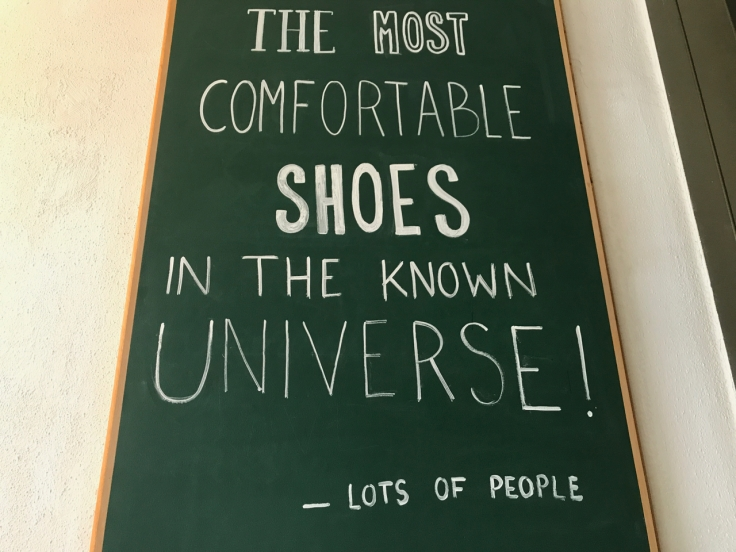 "A photo of a chalkboard sign that says, ""The most comfortable shoes in the known universe!"" The bottom of the sign says according to, ""Lots of People,"" spotted at Atheist Shoes in Berlin, Germany."