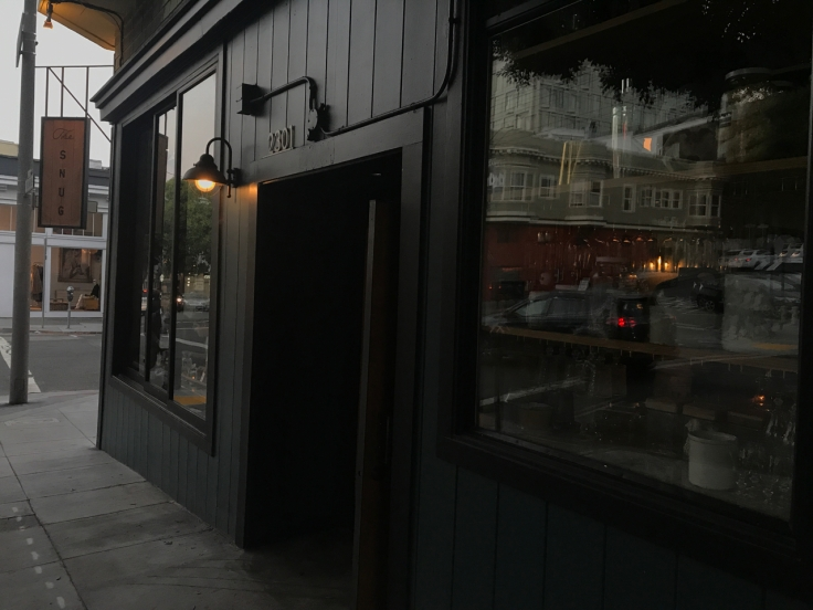 A street view photo of the outside of The Snug SF from the sidewalk in San Francisco, California.