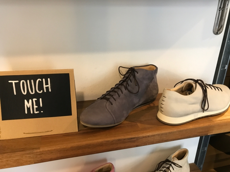 "A photo of a kitten testicle grey boot and a Nabakov cream sneaker on a wood shelf beside a sign that says, ""Touch me!"" at Atheist Shoes in Berlin, Germany."