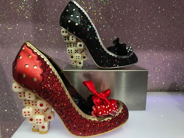 A photo of the up the ante high heels at Irregular Choice in London, England. The designs are in red and black glitter and the heel of each shoe is made out of dice.
