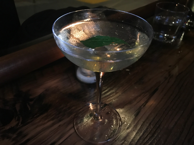 A photo of The Snug SF's Potent White Lily #2 cocktail in San Francisco, California. It's made with with gin, rum, orange liqueur, absinthe and curry leaf.