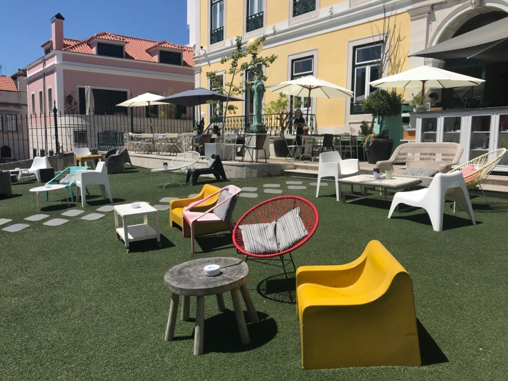 The cheery outdoor patio at Pharmacia restaurant in Lisbon, Portugal is filled with brightly colored chairs and tables.