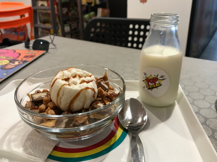 """A cereal bowl and a jug of milk sit on a cafeteria style lunch tray at Pop Cereal Café in Porto, Portugal. The item on the tray is the, """"#3. My Friends Call Me Caramel."""" It's Made With Nestlé Lion Cereal, Golden Grahams, Cookie Crisp, Caramel Chocolate, Toffee, Toffee Topping and Milk"""