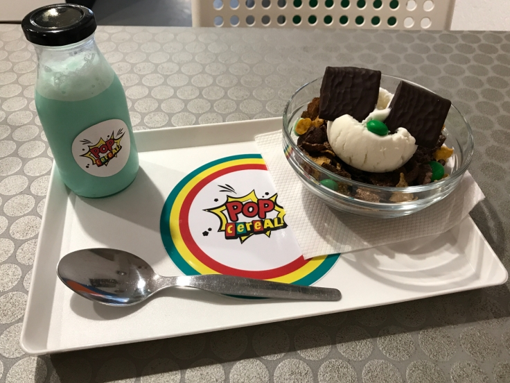 """On a cafeteria style lunch tray sits a jug of mint flavored milk and a cereal bowl at Pop Cereal Café in Porto, Portugal. The """"#4. Before and After Eight"""" is made with Clusters, Chocolate Crunchy Nut, Chocapic, After Eight Mint M&M's and Mint Flavored Milk. We added a scoop of cream flavored ice cream to it."""