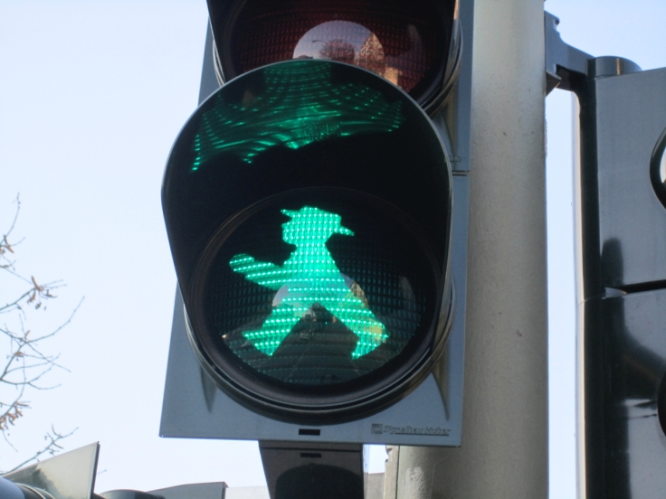A street traffic light in Berlin, Germany is lit up with a little green walking man which is called an ampelmännchen or ampelmann. Photo Courtesy of FoodWaterShoes