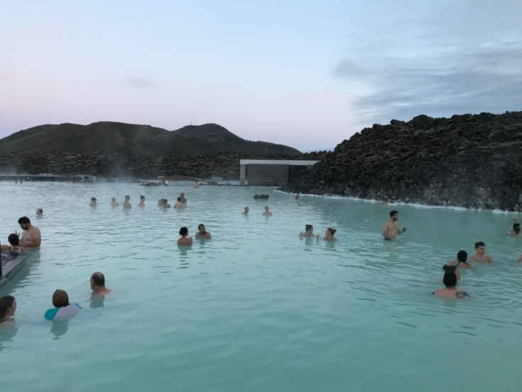 People swimming and bathing at sunset in the bright blue waters of Iceland's Blue Lagoon luxury geothermal spa just outside of Reykjavík in Grindavík, Iceland.