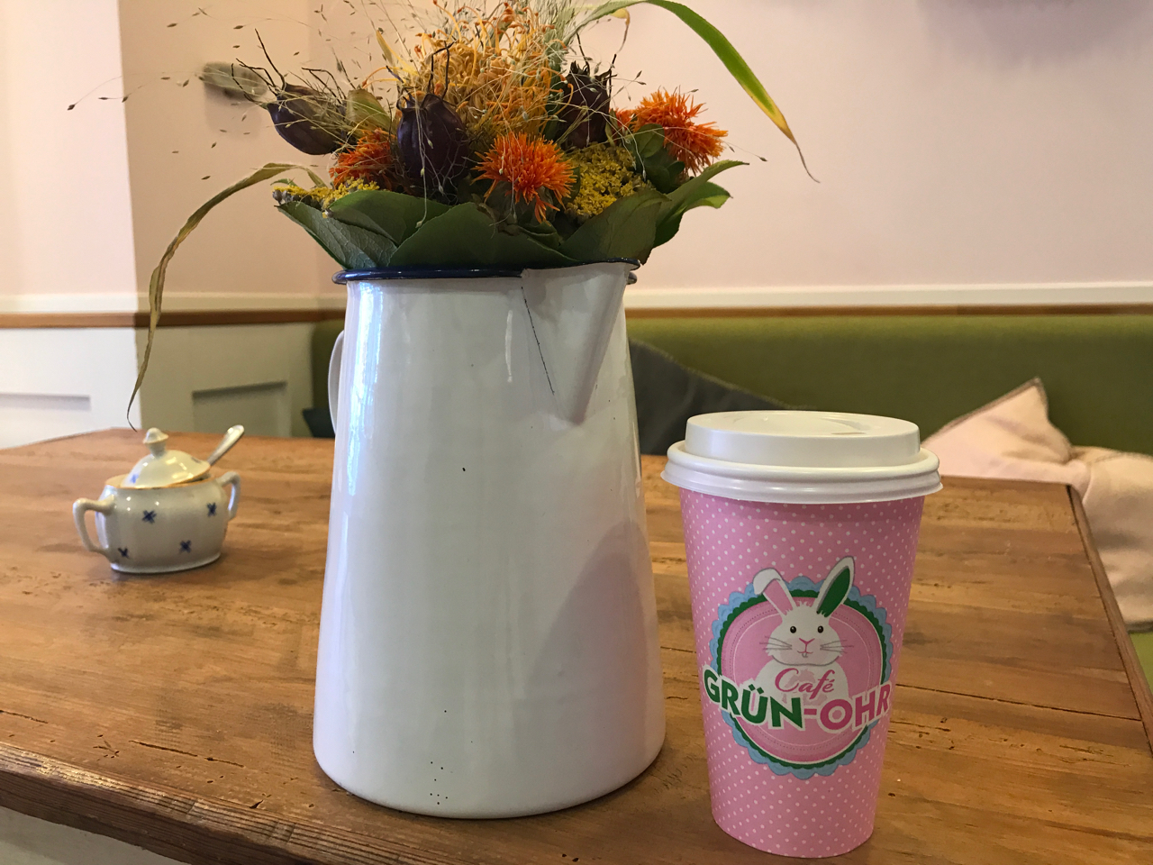 A cappuccino in Katjes Café Grün-Ohr's signature pink bunny cup in Berlin, Germany. The cup sits beside a bouquet of flowers in a pitcher on a wooden table. Photo Courtesy of FoodWaterShoes