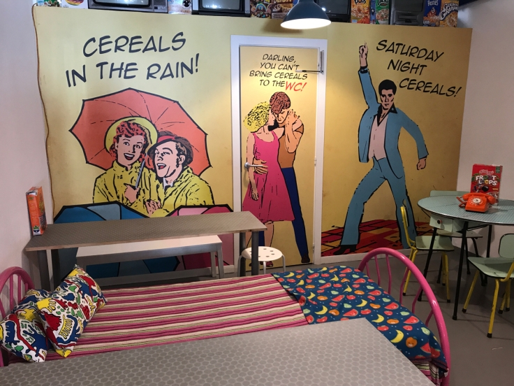 "Graphics on the wall at Pop Cereal Café in Porto, Portugal say, ""Cereals in the Rain,"" ""Darling, You Can't Bring Cereals to the WC!"" and ""Saturday Night Cereals!"" Seating options include beds as well as traditional restaurant tables and chairs."