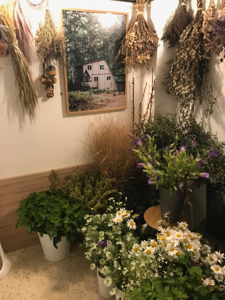 Bouquets of dried flowers hang from the ceiling at Peonies café and flower shop in Paris, France. Fresh bouquets of cut flowers sit on the floor.