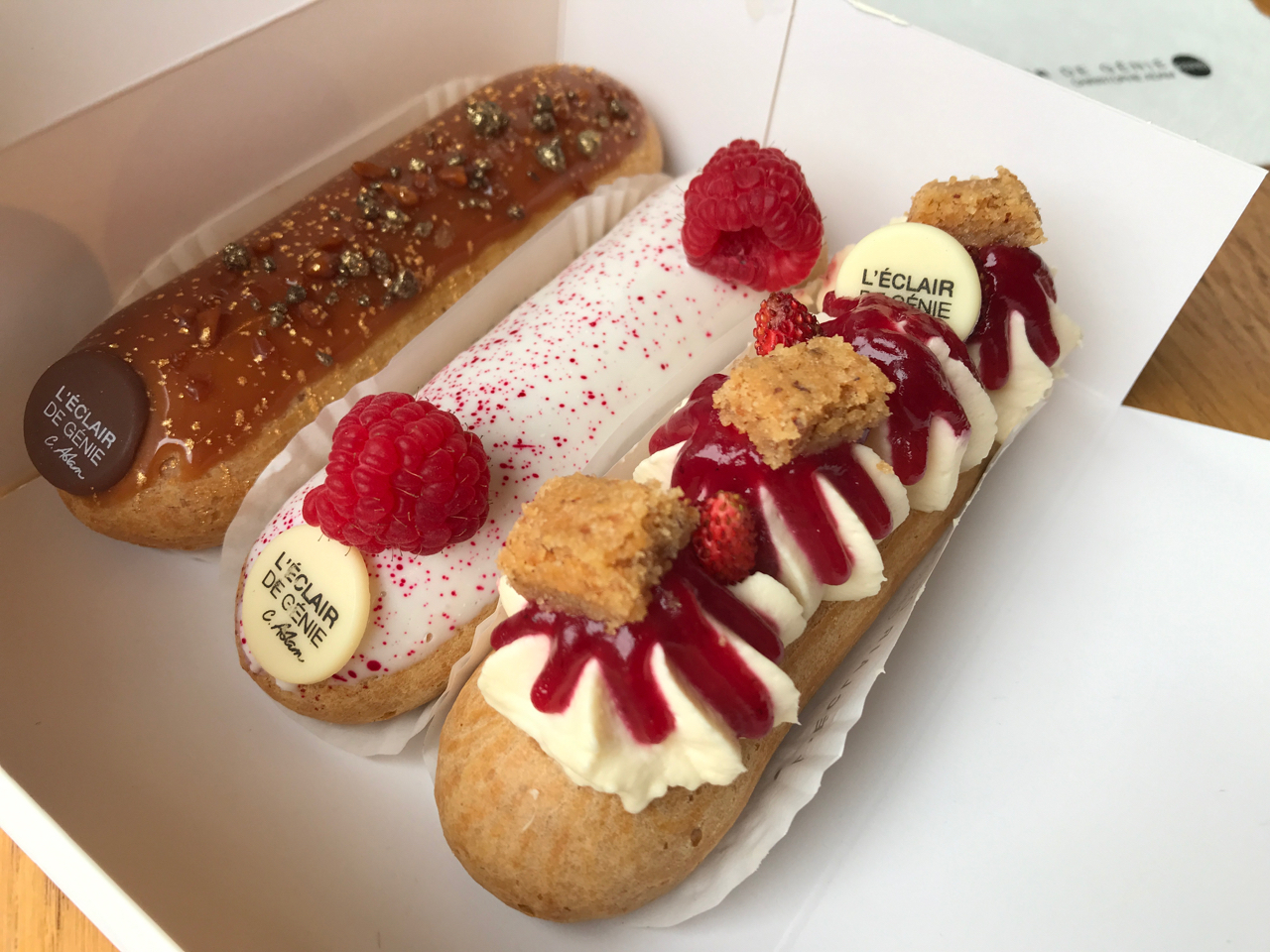 From left to right there are three delicious éclairs: salted caramel (caramel au buerre sale), rose lychee and raspberry mascarpone (rose, litchi et framboise mascarpone) and a wild strawberry éclair (fraises des bois). The three beautiful éclairs are sitting in a box from the La Fabrique location of L'Éclair de Génie's pastry shop in Paris, France. Photo Courtesy of FoodWaterShoes