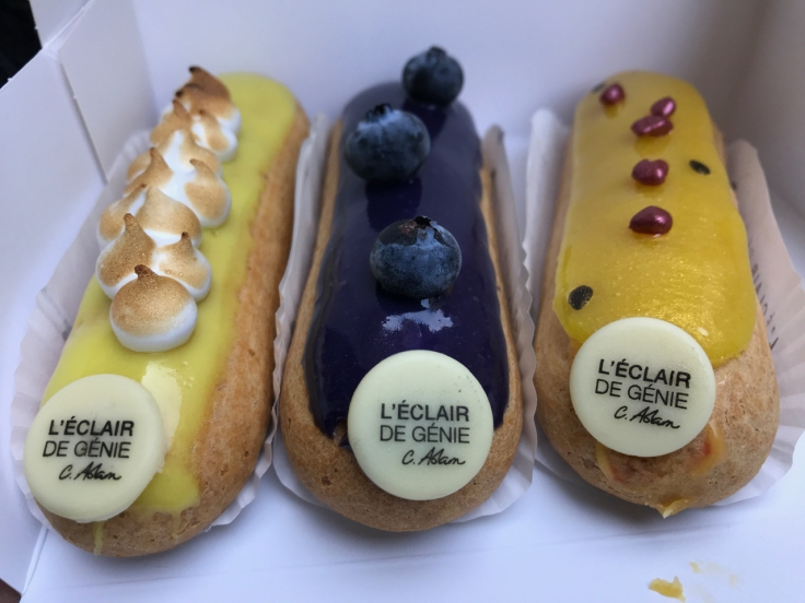 Lemon (citron), blueberry (myrtille) and raspberry passion fruit (framboise passion) éclairs from the Pavée location of L'Éclair de Génie pastry shop in Paris, France. Photo Courtesy of FoodWaterShoes