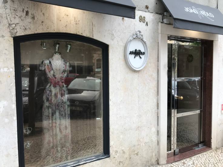 An exterior street view photo of the outside front of João Rôlo Couture (an haute couture dress and gown shop) taken from the sidewalk in Lisbon, Portugal. Photo Courtesy of FoodWaterShoes