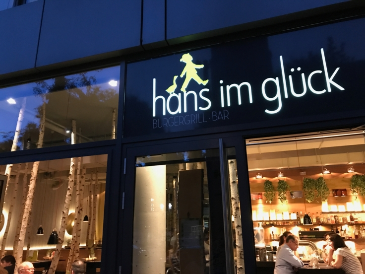 A photo of the exterior outside of Hans im Glück restaurant and burger grill in Stuttgart, Germany take from the sidewalk. Photo Courtesy of FoodWaterShoes