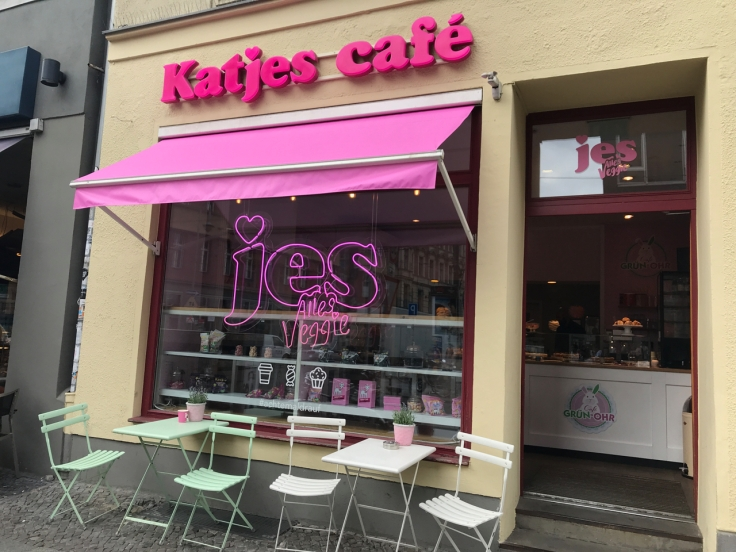 An exterior street view photo of the outside of Katjes Café Grün-Ohr as taken from the sidewalk out front. The cute coffee shop is located in Berlin, Germany. Photo Courtesy of FoodWaterShoes