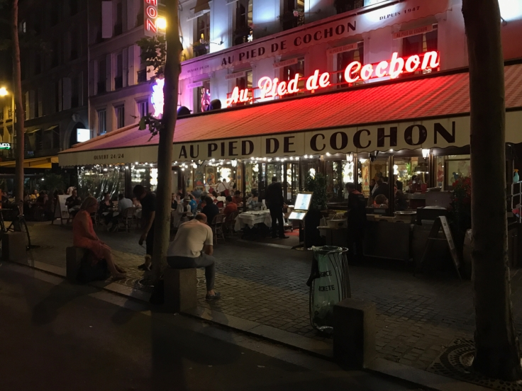 An exterior street view from the sidewalk outside of Au Pied de Cochon restaurant in Paris, France.