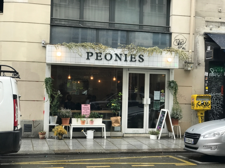An exterior street view photo of the sidewalk and the outside of Peonies café and flower shop in Paris, France.