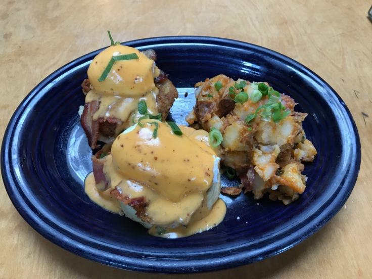 A breakfast dish of fried green tomato eggs Benedict with bacon and potato hash at Brenda's Meat & Three brunch restaurant in San Francisco, California.