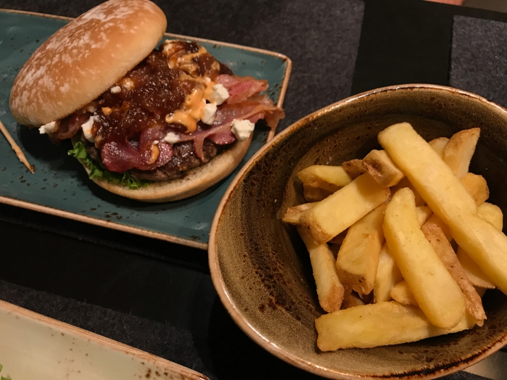 French fries nestle in beside a geissbock goat cheese, bacon and fig jam (ziegenkäse, speck, feigenmarmelade) burger at Hans im Glück burger grill and restaurant in Stuttgart, Germany. Photo Courtesy of FoodWatershoes