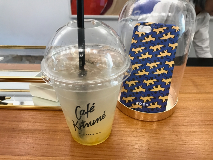 The iced yuzu drink at Café Kitsuné, a restaurant in Paris, France, sits beside business cards decorated with the house's signature fox design. Photo Courtesy of FoodWaterShoes