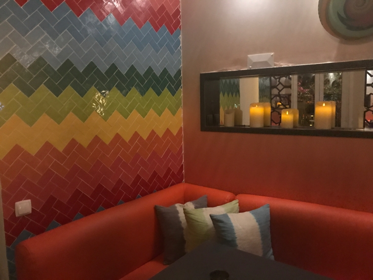 Inside Confraria Sushi in Cascais, Portugal there are rainbow tiles decorating the corner of the room. There's a red couch over which a mirror with candles is hung at the Japanese restaurant. Photo Courtesy of FoodWaterShoes