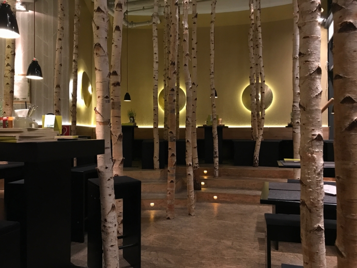 Tables in the restaurant are surrounded by a faux birch forest full or trees at Hans im Glück burger grill in Stuttgart, Germany. Photo Courtesy of FoodWaterShoes