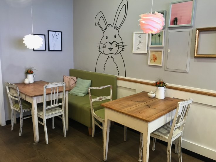 The interior tables and seating at Katjes Café Grün-Ohr coffee shop in Berlin, Germany feature their bunny rabbit mascot stenciled on the wall behind them. Photo Courtesy of FoodWaterShoes