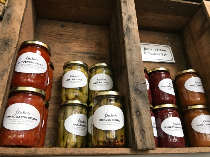 A shelf at Brenda's Meat & Three restaurant is crammed full of jams, pickles and sauces in San Francisco, California. There are jars of hot pepper jelly, pickled okra, spiced strawberry jam and peach cobbler jam that you can buy at this hip breakfast / brunch spot.