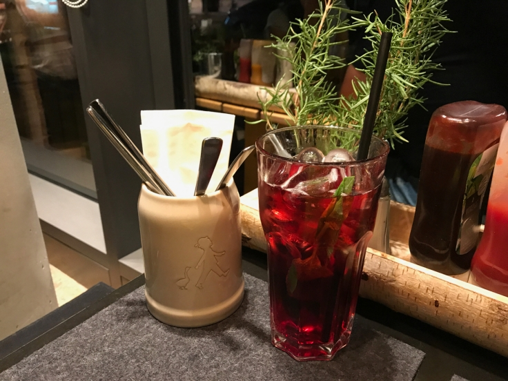 Beside a cure jar with a boy and a duck sits a johannisbeer basilikum (moranga lemonade with basil, currant and elderflower) at Hans im Glück burger grill in Stuttgart, Germany. The ruby red beverage sits is in front of a live little rosemary plant on the restaurant's table. Photo Courtesy of FoodWaterShoes