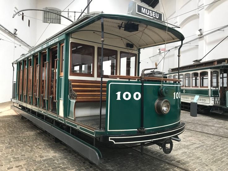An antique green trolley car sits inside the Museu do Carro Eléctrico in Porto, Portugal. The tram museum is located inside the Sociedade de Transportes Colectivos do Porto (STCP) building.