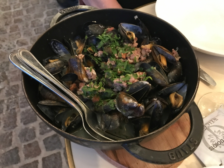 Steamed mussels (moules cochon façon hortense) in a cast iron dish are one of the many popular dishes you can eat at Au Pied de Cochon restaurant in Paris, France.