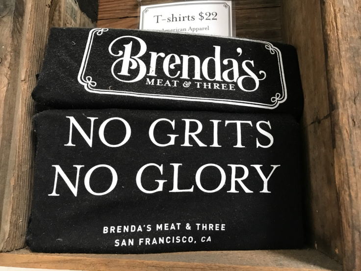 "A stack of black t-shirts on display at Brenda's Meat & Three says, ""No Grits, No Glory."" Brenda's Meat & Three is a trendy breakfast, brunch, lunch and dinner restaurant in San Francisco, California."