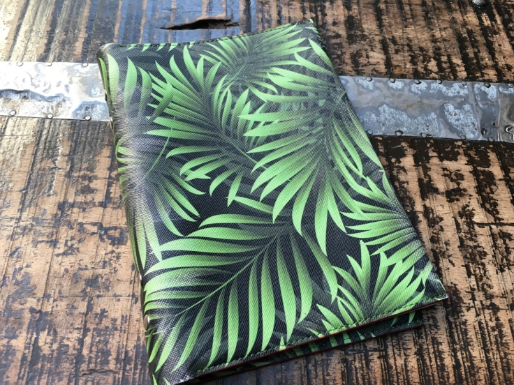 Beautiful green leather palm print menu covers decorate a table at El Jardín de SB (Salvador Bachiller) restaurant in Madrid, Spain.