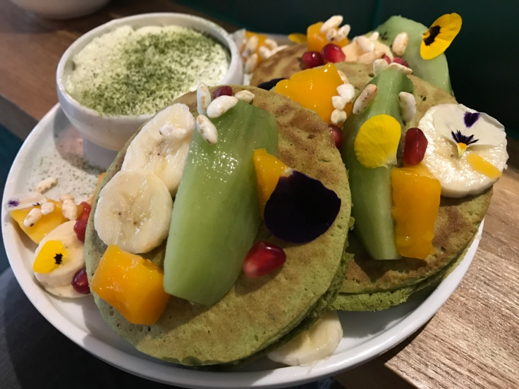 A plate is crammed full of three organic matcha pancakes (pancakes au matcha bio) at Peonies café and flower shop in Paris, France. The green pancakes are topped with flower petals, slices of banana, kiwi, pomegranate seeds and other brightly colored kinds of fresh seasonal fruit.