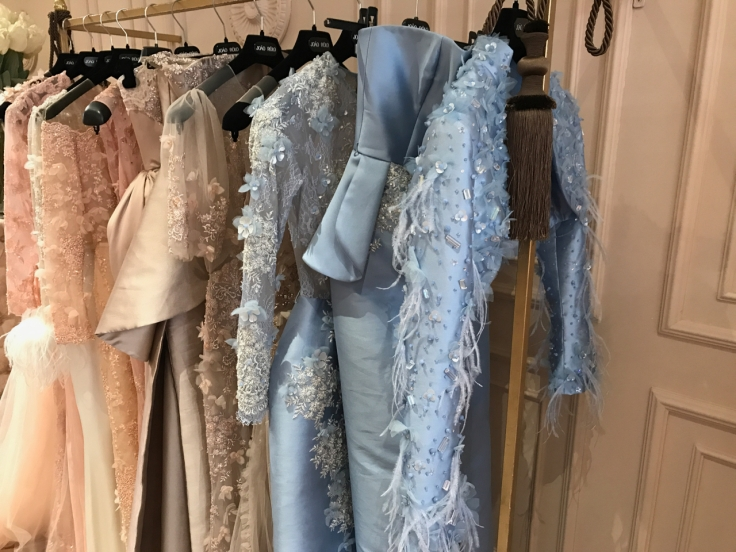 Feathered and beaded peach and baby blue dresses on display at João Rôlo Couture (a haute couture gown atelier in Lisbon, Portugal). Photo Courtesy of FoodWaterShoes