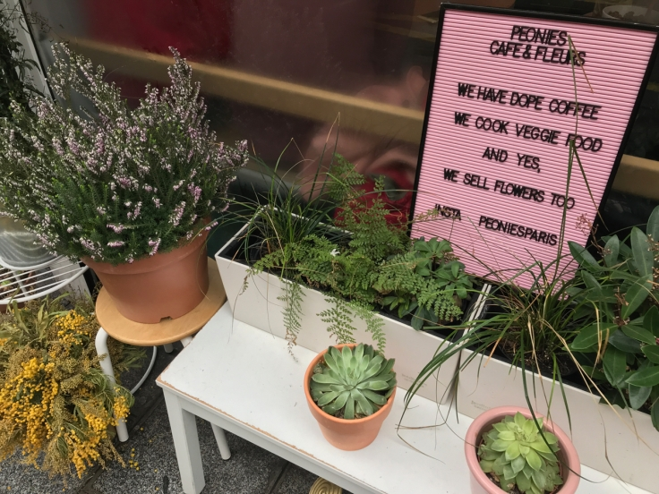 "A sign outside of Peonies coffee shop and florist in Paris, France says, ""Peonies Café and Fleurs - We have dope coffee, we cook veggie food and yes, we sell flowers too. Insta PeoniesParis"" The pink sign is surrounded by fresh flowers, plants and succulents."