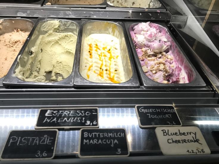 Containers filled with pistachio (pistazie), espresso walnut (espresso walnuss), buttermilk passionfruit (buttermilch maracuja), greek yogurt (Griechischer yoghurt) and blueberry cheesecake at Claus Eismanufaktur & Deli ice cream, gelato, sorbet shop, café and restaurant in Stuttgart, Germany.