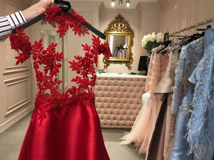 A gorgeous red gown with embroidered flowers that went to the 2018 Cannes film festival. João Rôlo Couture's Daniel Pinheiro is holding the dress by its hanger in the local Lisbon, Portugal boutique. Photo Courtesy of FoodWaterShoes